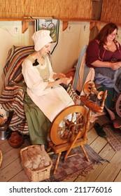 MUSKOGEE, OK - MAY 24: Ladies make yarn on spinning wheels at the Oklahoma 19th annual Renaissance Festival on May 24, 2014 at the Castle of Muskogee in Muskogee, OK