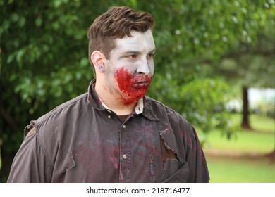 MUSKOGEE, OK - Sept. 13: A bloody male zombie walks in wait for the next runner to chase during the Castle Zombie Run at the Castle of Muskogee in Muskogee, OK on September 13, 2014.