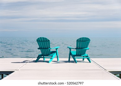 Merveilleux Muskoka Or Adirondack Chairs At The End Of A Pier Overlooking A Large Blue  Lake With
