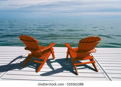 Muskoka or Adirondack Chairs at the end of a pier overlooking a large blue lake with a blue sky