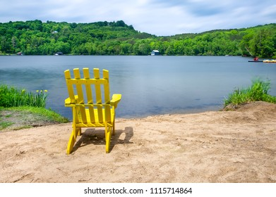 Muskoka chair on a sandy beach facing a lake. Across the calm water, cottages are nestled among green trees.
