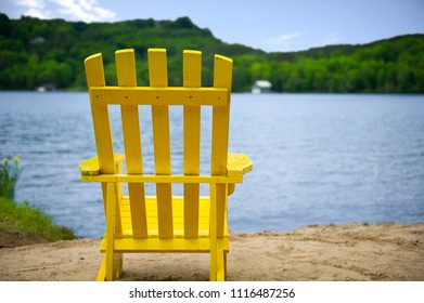 Muskoka chair on a sandy beach facing a lake. Across the calm water cottages are nestled among green trees.