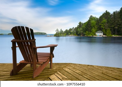 Muskoka chair sitting on a wood dock facing a lake. Across the calm water is a white cottage nestled among green trees. There is a boat dock on the water in front of the cottage.
