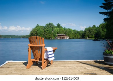 Muskoka chair sitting on a wood dock facing a calm lake. Across the water is a cottage nestled among green trees. A towel is folded on the chair arm.