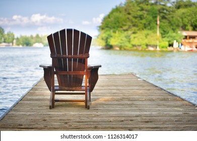 Muskoka chair sitting on a wood dock facing a calm lake. Across the water is a cottage nestled among green trees.