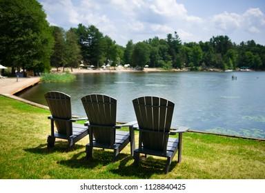 Muskoka chairs facing a calm lake. Across the water is a sandy beach.