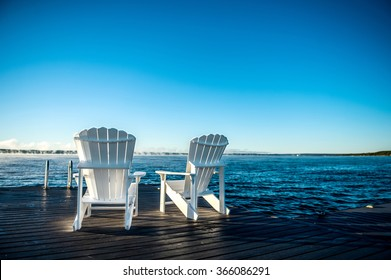 Muskoka chairs on a dock at a blue lake with a blue sunrise and mist coming off the water, closeup