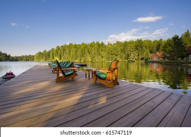 Muskoka chairs on a wood deck Muskoka chairs sitting on a wood dock facing a table with water glasses. A canoe is tied to the dock. Across the calm water there are cottages nestled among green trees.