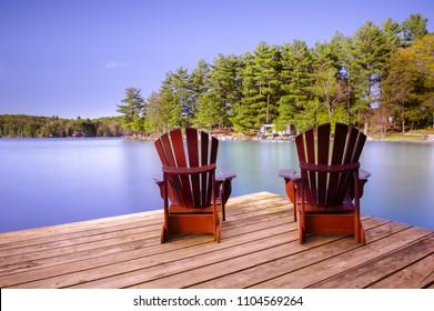 Muskoka chairs on a wooden dock facing a calm lake.