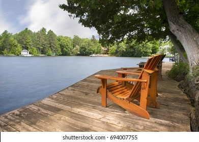 Muskoka chairs sitting on a wood dock facing a lake. Across the calm water are cottages nestled among green trees. Canada flag is visible