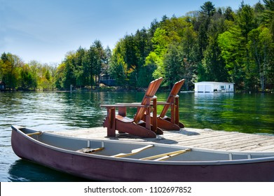 Muskoka chairs sitting on a wooden dock. Across the water there's a white cottage nestled between the trees. A canoe is tied to the dock.