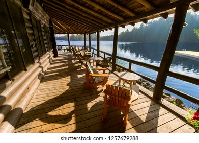 Muskoka chairs under a cottage wooden porch facing a calm lake.