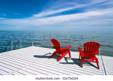 Muskoka or Red Adirondack Chairs at the end of a pier overlooking a large blue lake with a blue sky
