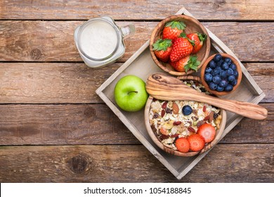 Musli in a wooden cup with nuts and different berries in a rustic box on a wooden background.Top view.Copy space