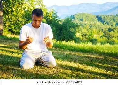 Muslim adult man praying outdoor at natrual environment sun beams