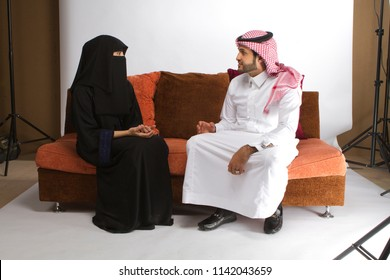 A muslim Arab couple sitting on couch having conversation in Saudi Arabia middle east gulf