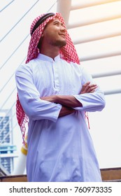 Muslim  Arab man. He standing and smile. He seeing sky and building background. Photo concept Arab man.