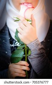 Muslim Arabic lady wearing Hijab and holding a rose