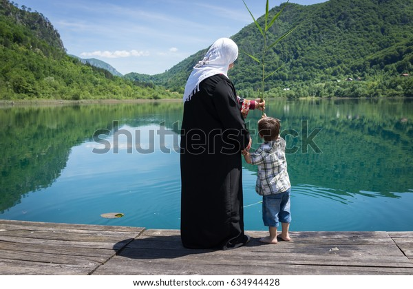 Muslim Arabic mother with her son on the lake