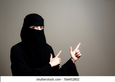 Muslim Arabic Woman Portrait Wearing Niqab and Pointing to a Subject.