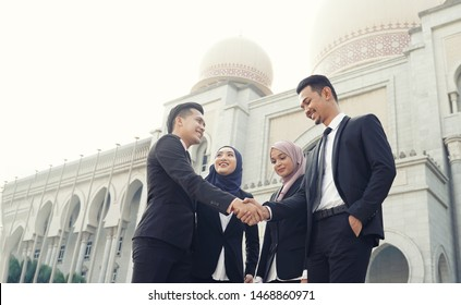 Muslim Asian business people shaking hands with new partner, business co-working teamwork concept. Successfull entrepreneur over a blur majestic building