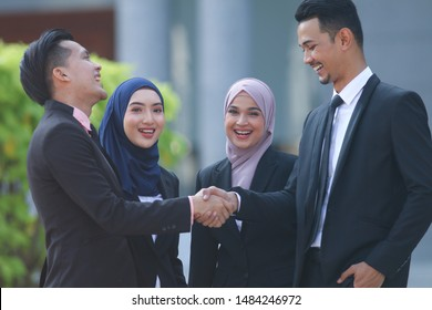 Muslim Asian business people shaking hands with new partner, business co-working teamwork concept. Welcome aboard!