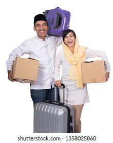 muslim asian couple with travel suitcase. going for ramadan eid mubarak celebration concept