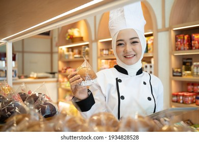 muslim asian female baker holding her product on the display tray