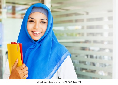 muslim asian girl, a college student, holding her workbooks in a class room