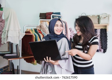 muslim asian woman entrepreneur team using laptop in her small fashion store