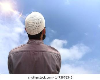 Muslim beard man looking at sky praying to Allah thinking about life