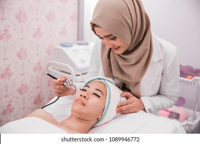 muslim beautician perform beauty treatment on woman face. applying oxygen therapy
