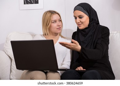 Muslim in black hijab and blonde woman sitting on sofa, using computer