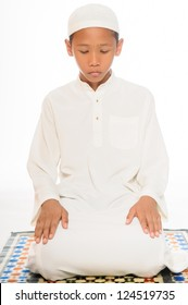 A muslim boy praying wearing islamic attire isolated on white background