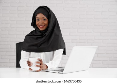 Muslim business lady working at computer in office. Pretty african woman in black hijab sitting at table, holding white cup, looking at camera and smiling. Concept of workplace.