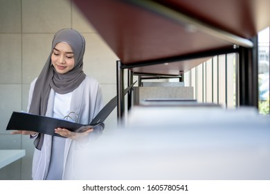 Muslim Business Woman in Hijab with Documents at Workplace in Office. Muslim asian female working in office.
