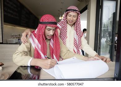 Muslim businessmen have meeting in cafe, coffee shop.