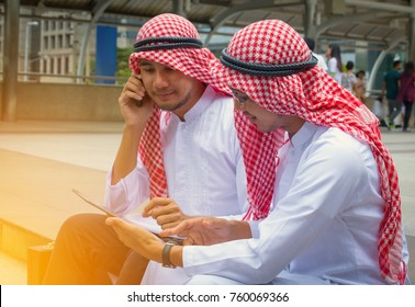 Muslim businessmen play smart phone. They are talking about business. building  background . Photo concept business.
