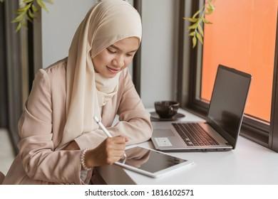 Empresaria musulmana con tablet en la oficina. Mujer musulmana asiática sonriendo y trabajando con tablet en el cargo