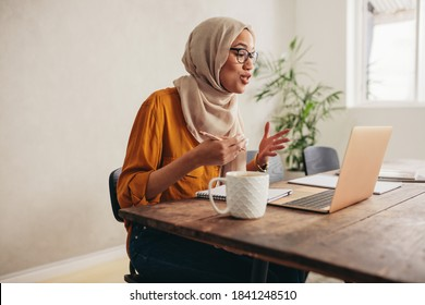 Muslim businesswoman working at home due to pandemic isolation. Female wearing hijab talking over a video call with team.