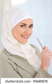 Muslim Caucasian female student holding pen