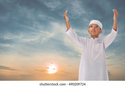 muslim child praying for Allah, muslim God on sky background