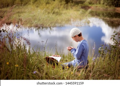 A Muslim child prays in nature near a beautiful lake.