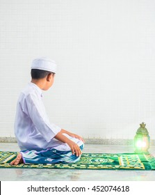 Muslim child worships and prays for Allah(muslim's God) , the prostate gestures are performed on carpet on the mosque floor
