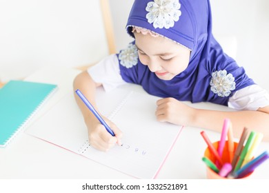 muslim children do homework in bedroom, Islam student learning English language,  education practice, she write A B C with her pen, Islamic children feeling happy and smile