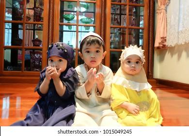 Muslim children praying Dua during Ramadan period to the God (Soft focus and film grain