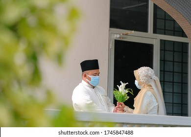 A muslim couple getting solemnization  in medical face masks during coronavirus pandemic. COVID-19 weddings. Social Distancing