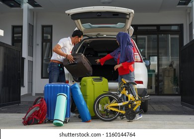 Muslim couple packing and loading luggages into car trunk for holiday
