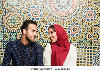 Muslim couple in relationship talking and smiling in front of arabesque oriental decoration