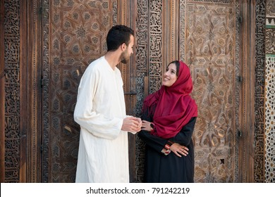 Muslim couple in relationship talking and smiling in traditional clothing